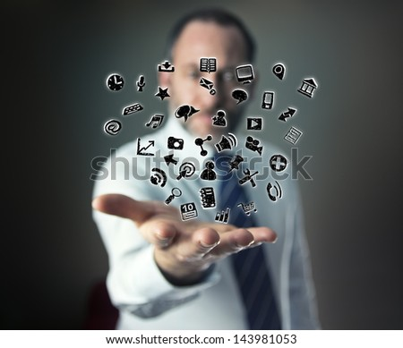 a mature businessman or salesman shows his hand with lots of apps flying arround