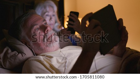 A mature Caucasian couple lying in bed at night engaged in the unhealthy habit of using smart devices at bedtime. Сток-фото ©