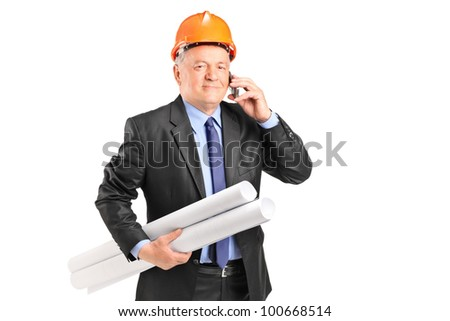 A mature construction worker holding blueprints and talking on a phone isolated on white background