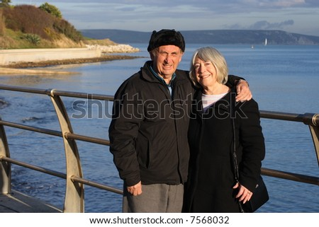 A mature couple enjoy a walk by the seaside in the winter.
