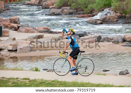 A mature cyclist takes a break by the river