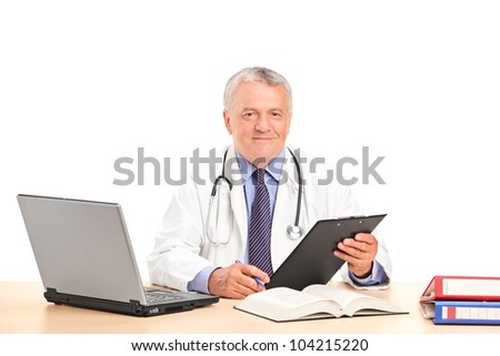 A mature doctor posing in his office isolated on white background - stock photo
