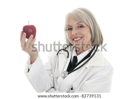 A mature female doctor wearing a stethoscope holds an apple.