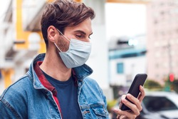 A mature handsome man with a beard chats on his phone and wears a face pollution mask to protect himself from coronavirus.