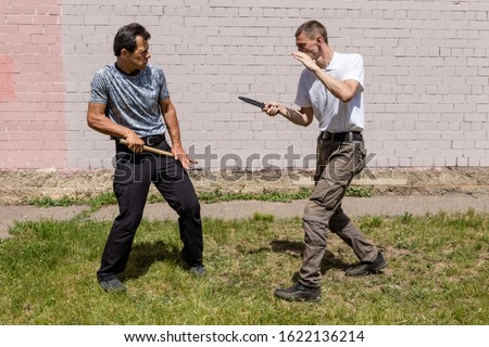 A mature man defends himself from a knife attack with a stick. Martial arts instructors demonstrate self-defense techniques of Krav Maga