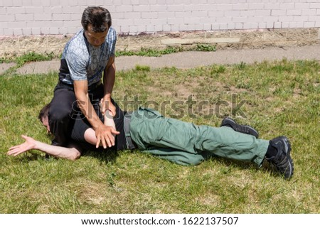 A mature man performs a painful technique to delay and fix the attacker. Martial arts instructors demonstrate self-defense techniques of Krav Maga