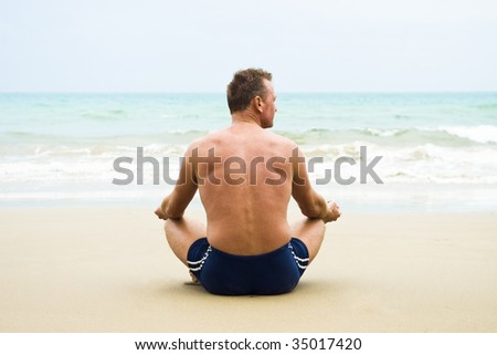 A mature man sitting cross legged on a sandy beach and meditating.
