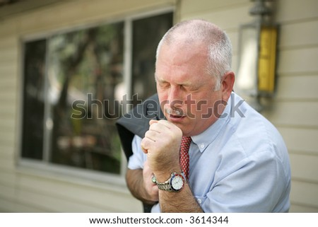 A mature man with a severe cough - probably the flu. - stock photo