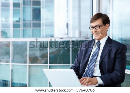A mature man with laptop in the office