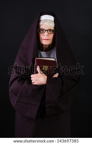 A mature nun holding a bible