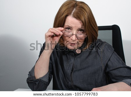 a mature pretty woman in glasses looking direkt questioning and criticizing