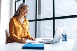 A mature satisfied asian gray-haired business woman wearing stylish casual clothes eyeglasses is using laptop for remote work, distance learning, online teaching