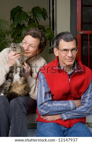 A mature woman lavishing all her attention on her cat, while her husband gets ignored.