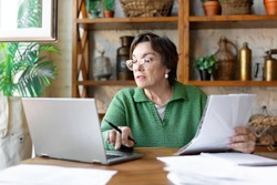 A mature woman while filling out documents. She uses an online tutorial to fill in the documentation correctly.