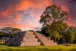 A Mayan pyramid next to a tree at the Copán Ruinas temples in a beautiful orange sunrise. Honduras