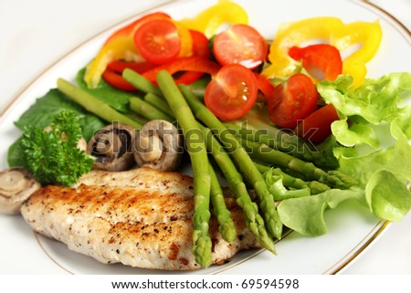A meal of fried fish with asparagus, boiled mushrooms and a salad of lettuce, rocket, cherry tomato and sliced capsicums