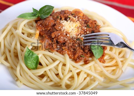 A meal of spaghetti bolognese garnished with basil leaves