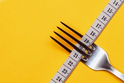 A measuring tape threaded through the fork on a yellow background. Good proper nutrition. Medical starvation. Diet for weight loss concept. Healthy lifestyle. Copy space.