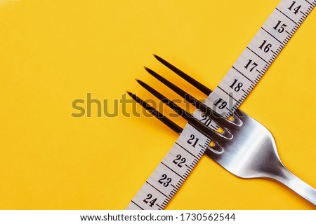A measuring tape threaded through the fork on a yellow background. Good proper nutrition. Medical starvation. Diet for weight loss concept. Healthy lifestyle. Copy space. Stock photo ©