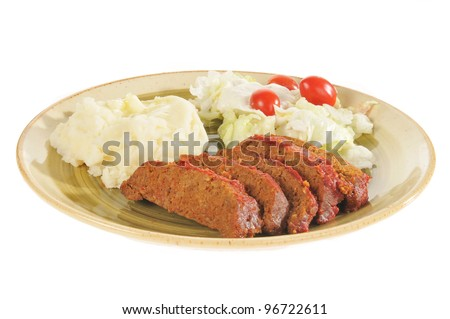 A meatloaf dinner on a white background