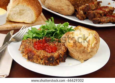 A meatloaf dinner with salad and baked potato