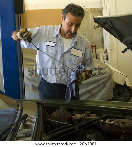 a mechanic checks the oil on a car being repaired - stock photo