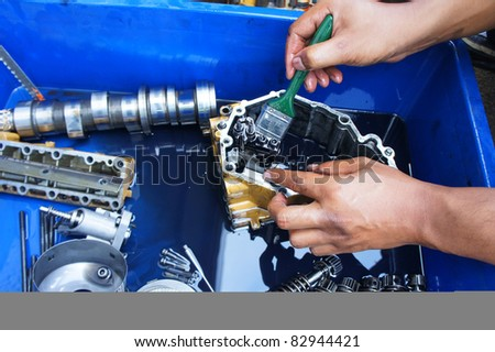 a mechanic cleaning the mechanical parts from automotive vehicle