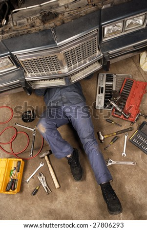 A mechanic doing repairs under the front of an old car from the early 80's. - stock photo