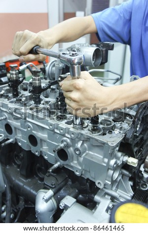 a mechanic fixing an automotive engines in lab