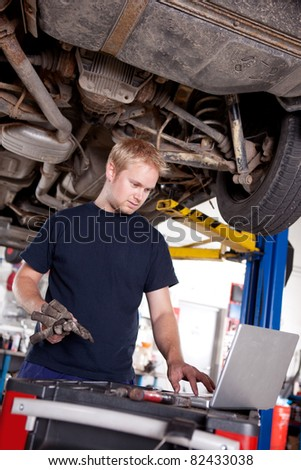 A mechanic in a garage looking at a laptop