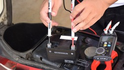 A mechanic is measuring the voltage of a motorcycle battery with clamp meter for maintenance. Thai text is mean