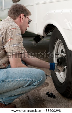 A mechanic is performing a safety check and tightening the lug nuts on the wheels of a truck.