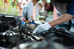 A mechanic is repairing a car about the engine's valve system.