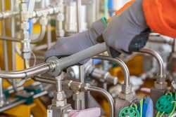 A mechanic operator fix and tighten stainless steel tubing system by using combination wrench, offshore oil and gas industry maintenance and service business.