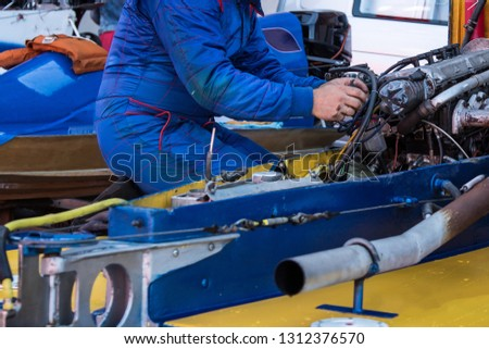 A mechanic prepares a racing boat for Championship. #1312376570