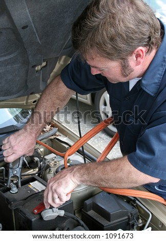 A mechanic using jumper cables to start a car battery.  Vertical.