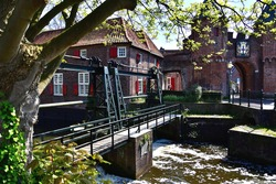 A mechanical floodgate which guides your view to the medieval and beautiful colored citycenter and gate of Amersfoort. The picture is framed by a tree and it's foliage.