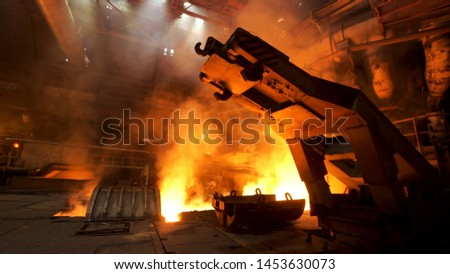 A mechanism with hooks in the hot shop with rising smoke and burning fire at the metallurgical plant. Stock footage. Heavy industry, equipment at the steel factory.