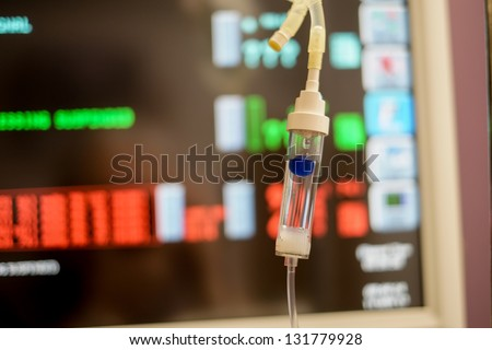 a medical IV intravenous drip and medical monitors in a hospital emergency room