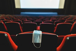 A medical mask hangs on a chair in an empty cinema hall. Pandemic and crisis in the industry. Delayed movie premieres