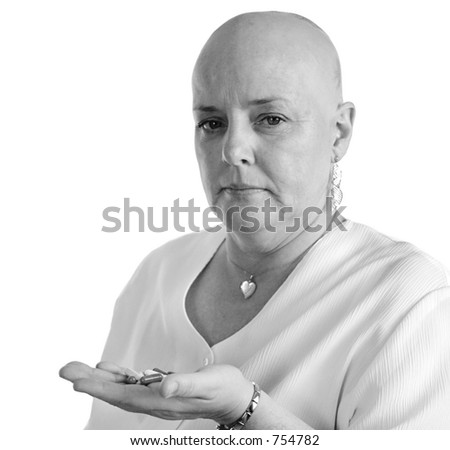 A medical patient holding a handful of pills and looking disgusted she has to take them.