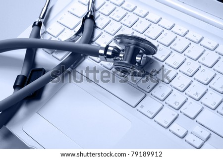 A medical stethoscope on a laptop, closeup