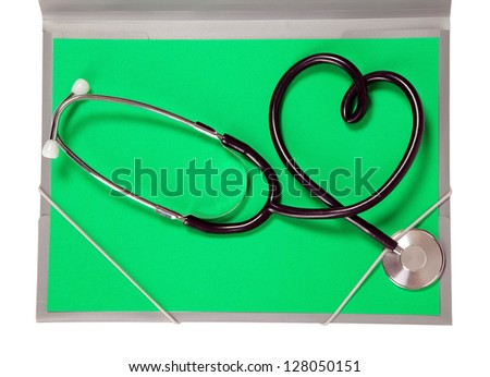 A medicine stethoscope is lying on green paper