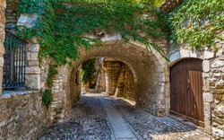 A medieval alley under a stone bridge in an old village in Italy
