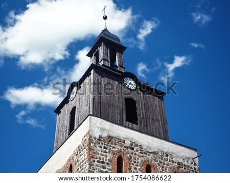 A medieval catholic church (Kościół pw. św. Ducha) with a clock tower against blue sky with white clouds, Moryn Poland Zdjęcia stock ©