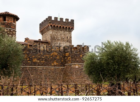 A medieval looking castle with towers on a gloomy winter day with olive trees on either side and bare grape vines along a fence.