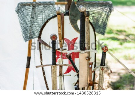 A medieval old group of swords and knights equipment. Close up of handles sword and blurred shield in the background. Medieval and historical concept. Selective focus. #1430528315