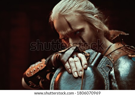 A medieval warrior in armor drinks from a flask by candlelight. Stage portrait. The Witcher man. Zdjęcia stock ©