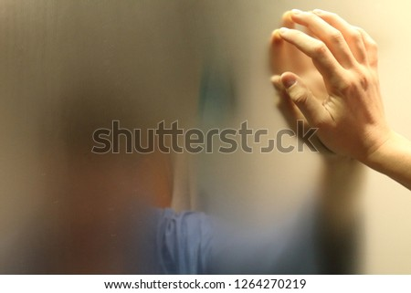 A meditative man with a blue bathrobe in a bathroom watching himself in a foggy blurry mirror and resting his hand on it, in an introspective moment