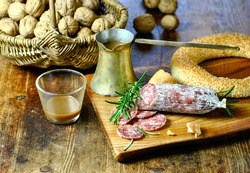 A Mediterranean stilllife. Breakfast with salami, rosemary and sesame bread on rustic wooden table. A basket of walnuts in the background. Brass coffee pot and a glas with a last sip of coffee